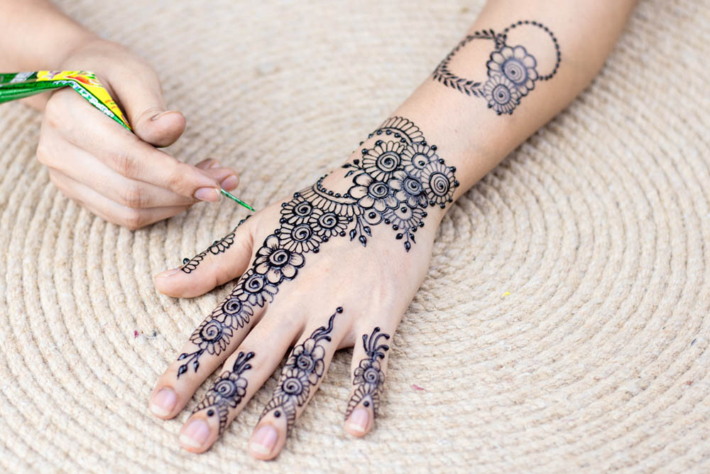 A person's hand painting henna tattoo on the other hand.